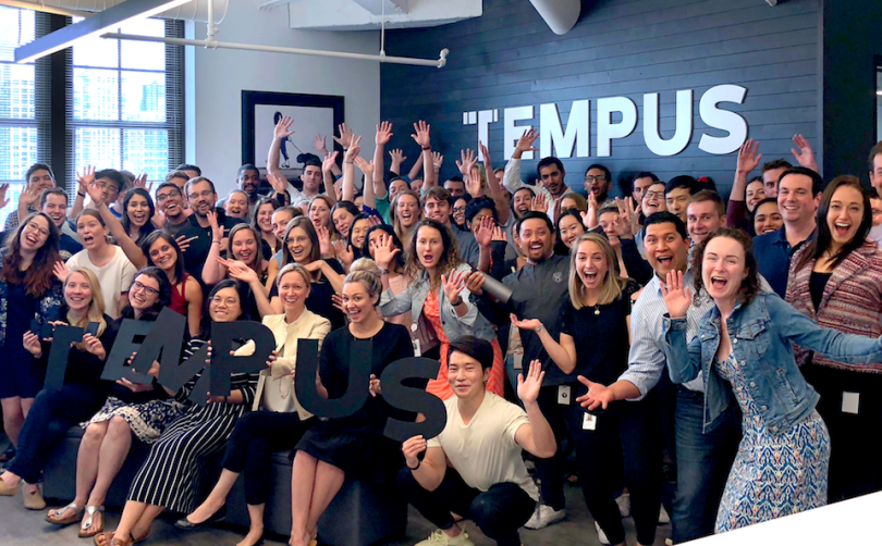 Tempus staff smiling and waving in office