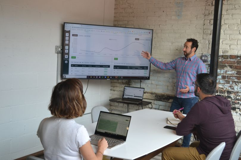 A team of analysts at ClearCut gather around a line graph of data to discuss strategy.